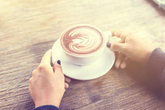 Girl holding a cup of coffee on a wooden table Stock Photo