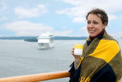 Girl holding cup on deck of ship Royalty Free Stock Photography