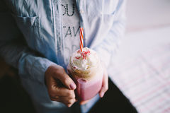 Girl is holding cup of pink coffee with cream, marshmallow and decoration. Milk shake, cocktail. Unicorn coffee, unicorn food. Stock Photos