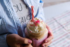Girl is holding cup of pink coffee with cream, marshmallow and decoration. Milk shake, cocktail. Unicorn coffee, unicorn food. Royalty Free Stock Photo