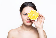 Girl holding a cut orange in front of eye Stock Photo