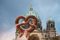 The girl is holding a delicious traditional German pretzel. In the hand against the backdrop of the Berlin Cathedral is called Berliner Dom. Berlin, Germany stock photos