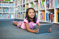 Girl holding digital tablet in school library. Portrait of girl holding digital tablet while lying in school library Royalty Free Stock Photos