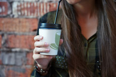 Girl holding a disposable coffee cup. On a background of a brick wall Royalty Free Stock Photo