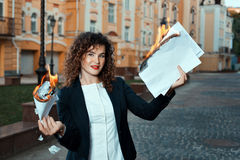 Girl is holding the documents that burn. Stock Photos