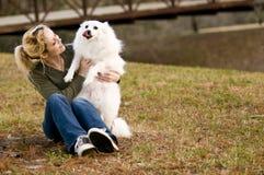 Girl holding dog Stock Images