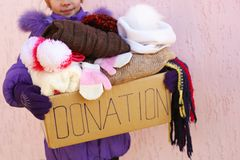 Girl holding donation box with winter clothes royalty free stock image