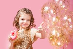 Girl holding donut and gesturing thumb up. Cute girl in golden glittering dress holding donut and gesturing thumb up on pink background Stock Photo