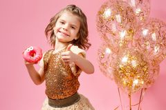 Girl holding donut and gesturing thumb up. Cute girl in golden glittering dress holding donut and gesturing thumb up on pink background Royalty Free Stock Photography