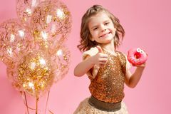 Girl holding donut and gesturing thumb up. Cute girl in golden glittering dress holding donut and gesturing thumb up on pink background Royalty Free Stock Photos