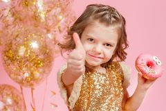 Girl holding donut and gesturing thumb up. Cute girl in golden glittering dress holding donut and gesturing thumb up on pink background Royalty Free Stock Images