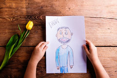 Girl holding drawing of her father and yellow tulip. Royalty Free Stock Image
