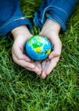Girl holding Earth in hands against green grass Stock Photo