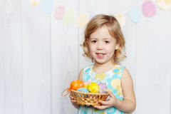 Girl holding Easter basket. Happy little girl holding Easter eggs stock image