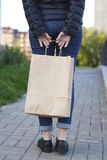 Girl holding ecological shopping with paper bag in hands. Royalty Free Stock Image
