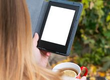 The girl is holding an electronic book and tea with lemon. E-book closeup with a place for the inscription, which is held in the hand by a girl and drinks tea Royalty Free Stock Photos