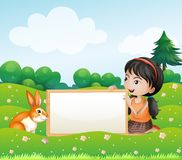 A girl holding an empty blank board with a rabbit Stock Photography