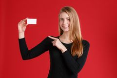 A girl holding an empty business card and showing a finger at it. On a red background. royalty free stock photography