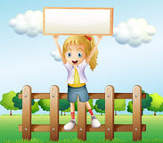 A girl holding an empty frame standing above the fence Stock Photography