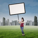 Girl holding empty poster at field Stock Image