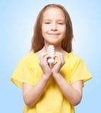 Girl holding an energy saving lamp Stock Photo