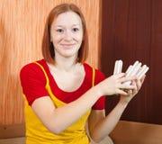 Girl holding an energy saving light bulbs. Girl holding an energy saving compact flourescent light bulbs stock photos