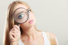 Girl holding on eye magnifying glass loupe Royalty Free Stock Photos