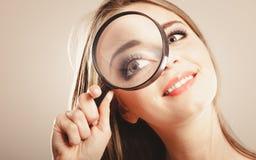 Girl holding on eye magnifying glass loupe Stock Photo