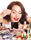Girl holding eyeshadow and makeup brush. Stock Photos