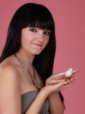Girl holding fake bird. Cute young woman holding a fake white bird, pink background Royalty Free Stock Photo