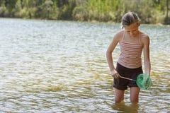 Girl Holding Fishing Net In Lake Stock Photo