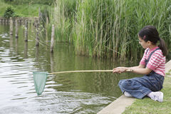 Girl Holding Fishing Net At River Royalty Free Stock Image