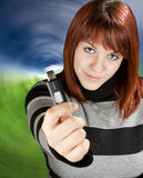 Girl holding a flash drive. Beautiful redhead girl holding an usb memory stick or flash drive at the camera. Studio shot royalty free stock photos