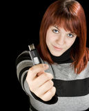 Girl holding a flash drive. Beautiful redhead girl holding an usb memory stick or flash drive at the camera. Studio shot royalty free stock image