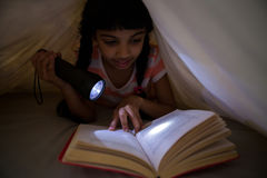 Girl holding flashlight while reading novel under blanket Stock Image