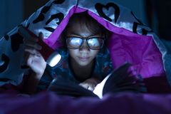 Girl holding flashlight while wear glasses reading books blanket in bed room stock image