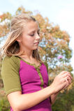 Girl Holding Flower. Pretty teenage girl holding a clover bloom Stock Photo