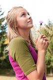 Girl Holding Flower. Pretty teenage girl holding a clover bloom Royalty Free Stock Images