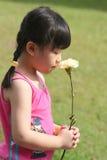 Girl holding flower. Girl holding & smeeling a flower, yellow carnation Stock Image