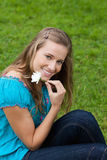 Girl holding a flower next to her face Stock Photography