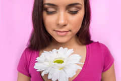 Girl holding flower on pink background. Royalty Free Stock Photography