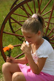 Girl Holding Flowers. Girl sitting in front of a wheel holding flowers royalty free stock photos