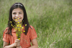 Girl Holding Flowers In Field Royalty Free Stock Photography