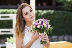 Girl holding flowers in hands, young beautiful bride in white dress holding wedding bouquet, bouquet of bride from rose cream spra stock image