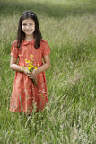 Girl Holding Flowers In Meadow Stock Images