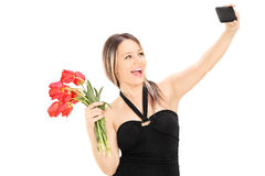 Girl holding flowers and taking a selfie Stock Images