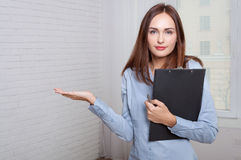 Girl holding a folder expressing bewilderment Royalty Free Stock Image