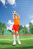 Girl holding football on both straight arms Royalty Free Stock Photos