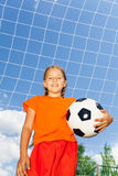Girl holding football in one arm standing Stock Images