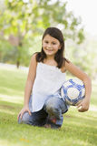 Girl holding football in park Royalty Free Stock Photo